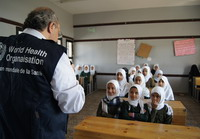 Dr Osama Mere with a classroom of children