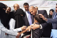 A boy being vaccinated by health workers assisted by Amin Joma'an, Secretary-General of the Sana'a local council