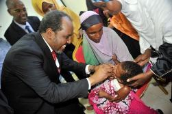 The President of Somalia giving a vitamin A supplement to a baby