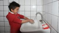 A young boy washes his hands with enthusiasm