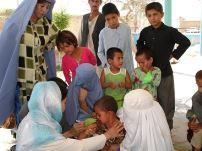 A child receives a measles vaccination during WHO's post-disaster campaign in flood-affected provinces