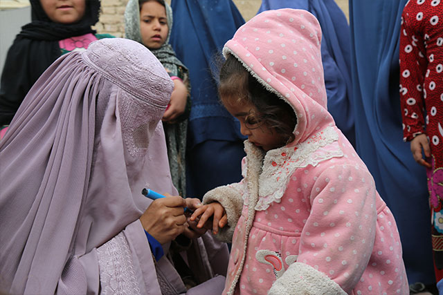 A girl looks on as her finger is marked after vaccination