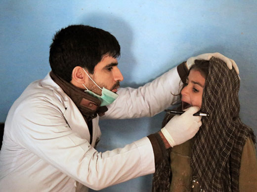 "Credit: WHO Afghanistan/S.Ramo Dr Saleh Ahmad checks 7-year-old Nasima's teeth at a mobile clinic at the Pul-e-Company IDP camp. Nasima's family fled the conflict in Kunduz a year ago and they have been living in the camp since then. ""This is a very busy clinic, I see on average 100 patients a day,"" Dr Saleh says. ""The main health problems are respiratory infections, diarrhoea, eye infections. People here also suffer a lot from mental health issues and anxiety. These cases we sometimes refer outside to bigger government hospitals that have the capacity to provide treatment, but it is not always easy for IDPs to access services there."""