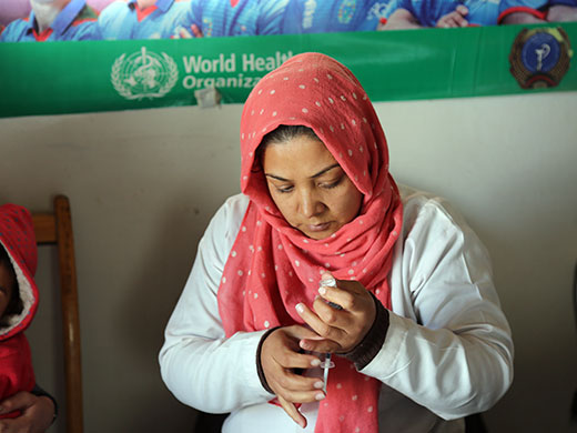 """Credit: WHO Afghanistan/S.Ramo Elina prepares the inactivated polio vaccine (IPV) to administer to Maryam, a 3-year-old Afghan refugee returning from Pakistan. In 2016, over 122 000 returnee and refugee children were vaccinated with OPV and over 32 000 with IPV with the support of WHO. Elina has worked as a vaccinator for 3 years. """"I am a mother of 3 daughters and really enjoy my job as a nurse and vaccinator. I want to help our children and make sure all Afghan children can be spared from polio paralysis by giving them the polio vaccine."""""""