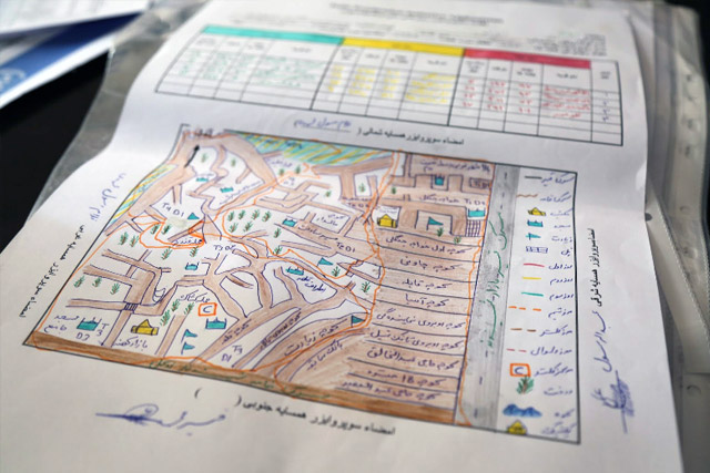 "Before each vaccination campaign, polio programme draws detailed maps of where each team will head. These maps are called ""microplans"", and they show streets, landmarks and each house where vaccinators need to visit during the campaign days. Dr Zalmai Ataie and Dr Esmaiel Sadiqi examine a map in the Herat regional office."