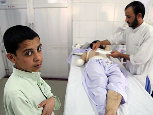 Credit:� WHO Afghanistan/G.Elham The son of Jalad Khan, 43, stands by his bedside as he is treated at the Emergency hospital. Jalad Khan was hit by a landmine. Many of the patients come from other districts of Helmand where war rages on. In the past year through ECHO funding, WHO supported 6 first aid trauma posts in the province. These trauma posts provide life-saving first aid and stabilize trauma victims, and they are connected to Lashkar Gah's Surgical Centre by a free ambulance service operating 24 hours a day, 7 days a week.