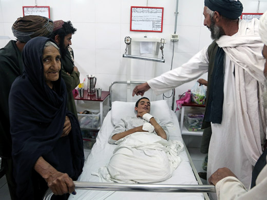 "Credit:� WHO Afghanistan/G.Elham 60-year-old Nazo stands at the bedside of his grandson Rahmatullah, 19, who was badly injured by a roadside bomb in Lashkar Gah. Rahmatullah lost both of his legs in the blast, and received treatment at the Surgical Centre. ""There is a fight going on everywhere and you can hear gun shots from everywhere. I fear that peace will never come,"" Nazo says."