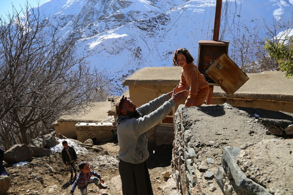 Uncle Arsalan Khan helping Khadija, 4 years old, to climb down the wall in Doshakh village, Rukha district of Panjshir province. Photo: Ahmadullah Amarkhil/WHO Afghanistan