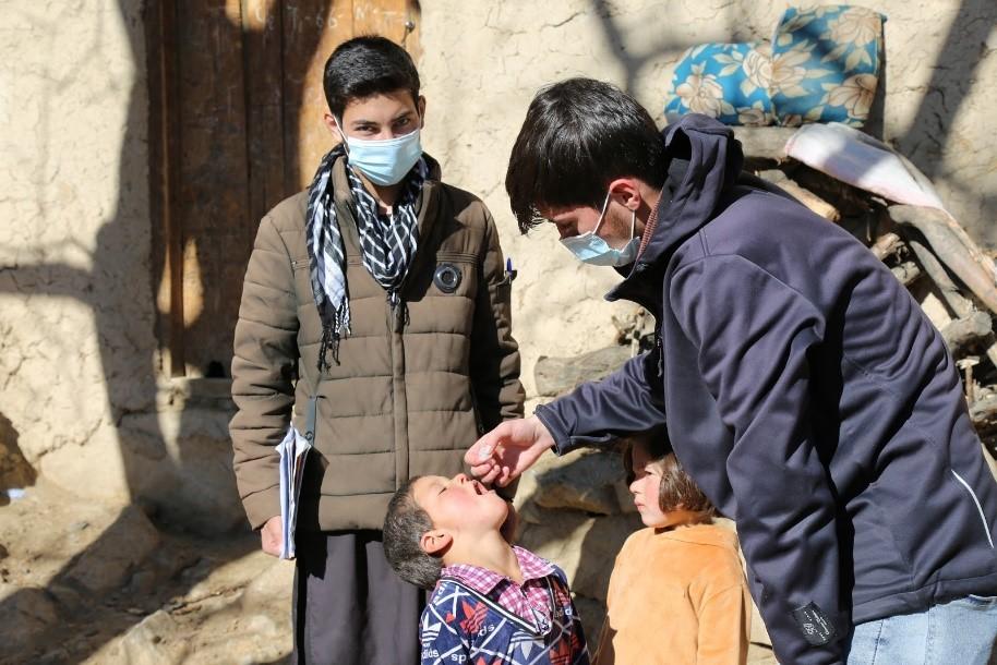 Volunteers, Ziaullah and Navid Ahmad, giving polio drops to Sanaullah and Khadija. Doshakh village, Rukha district, Panjshir province. Photo: Ahmadullah Amarkhil/WHO Afghanistan