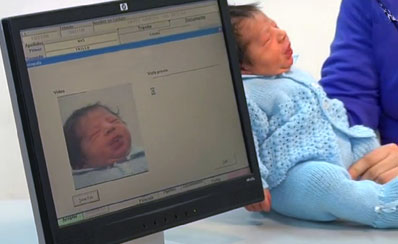 A baby being held next to a computer. The baby's image is reflected on the screen of the computer.