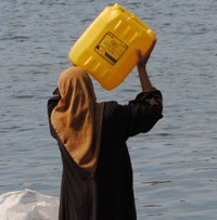 A photograph of a woman carrying a large water container