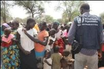 A large group of South Sudanes women and their children with a WHO staff member in the foreground