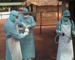 A photograph of three laboratory technicians wearing protective facial masks, gowns, eye visor and gloves while securing a sample container