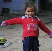 A photograph of a young girl spreading out her arms and smiling at the camera