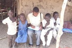 A surveillance officer sitting in the middle of a group of children and taking notes