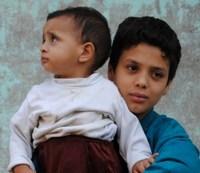La foto ens mostra un adolescent amb un nen petit en els seus braços