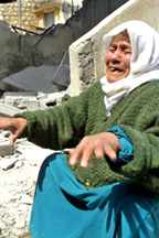 A picture of a veiled older woman in anguish sitting near the steps of a ruined property
