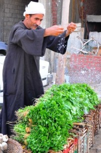 Street vendor splashing his green leafy vegetables with water