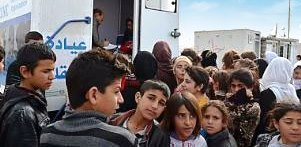 Young Iraqis wait outside a mobile clinic for medical services in Iraq