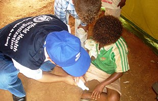 A WHO staff member tends to a young child