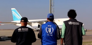 WHO and World Food Programme staff watch the plane take off carrying eight mobile clinics donated by Saudi Arabia