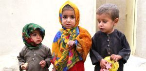 Three children show dots of ink on their fingers which show that they were reached with polio vaccines during a polio vaccine on the outskirts of Kandahar city