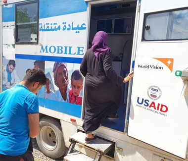 Bashtapa Mohammed, a displaced mother of 3 enters a mobile medical clinic to access health services in Qoratu