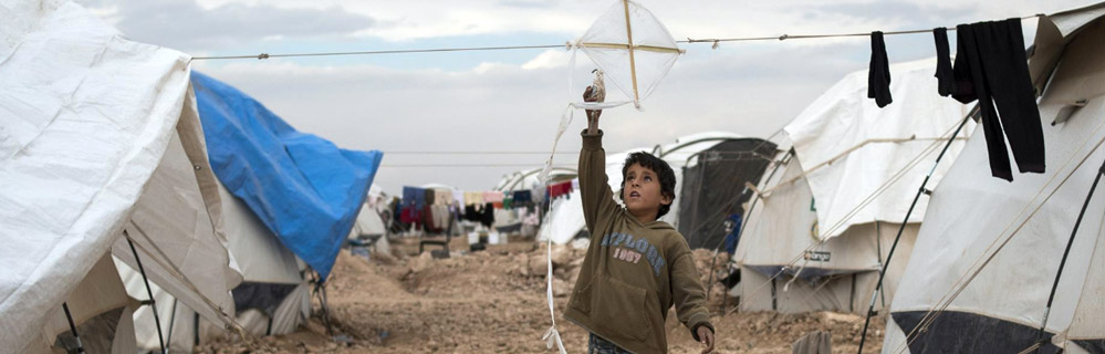 refugee child flies kite in camp