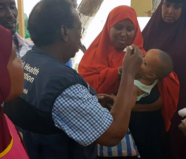 Shire from Somalia vaccinating a child