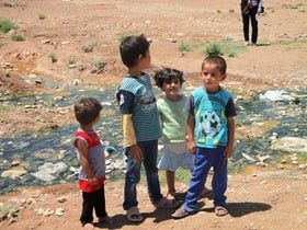 Four young children in Iraq stand in front of a site strewn with rubbish