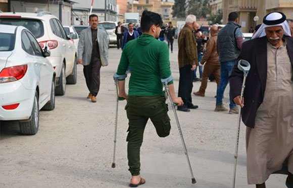 Ahmed Jamil makes his way down the street with the use of crutches