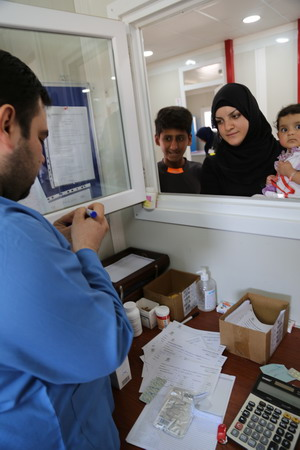 A patient receives medicine at a health facility in Qayara supported by one of the health cluster partner