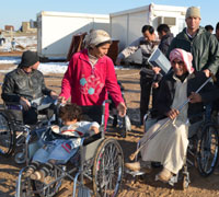 Syrian refugees receiving wheelchairs in the Domiz camp