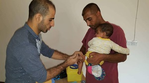 WHO-supported mobile medical team member vaccinates a child in Hawiija district