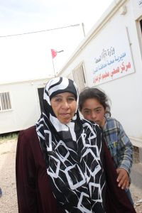 Fatmah, a 14-year-old Syrian refugee, stands behind her mother at Al Zaatari camp