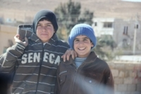 Two young Jordanian boys smiling at the camera