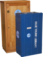 Picture of a blue trunk library in front of a mini library contained in a wooden chest