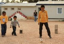 Three young boys playing football