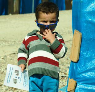 Boy holds information leaflet during cholera campaign in Iraq