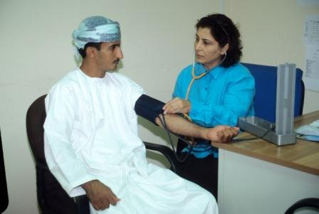 A female nurse in Oman testing the blood pressure of a male patient