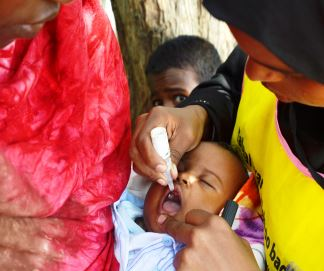 A child receives just two drops in the mouth of the poilio vaccine during a vaccination campaign
