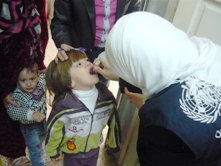 A child is administered oral polio vaccine in Homs
