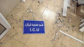 A sign for the intensive care unit lies on the floor of a damaged hospital