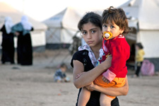 A young girl holds her younger sister against the backdrop of a Syrian refugee camp