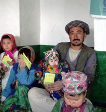 A man from Afghanistan proudly displays his vaccination card in the presence of his children