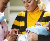 A health care worker vaccinates a baby held by its mother