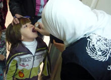 A Syrian child receives polio vaccine during the campaign