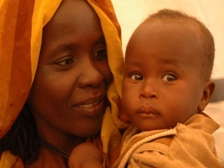 A Sudanese mothers smiles at her child in her arms