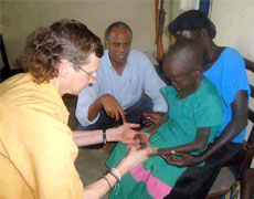 Health workers in Uganda examine a young girl showing symptoms of nodding syndrome
