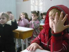Children in a Homs kindergarten hold up their hands to show they have been vaccinated